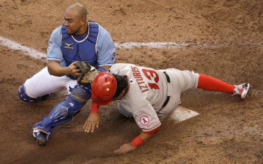 The Angels' Maicer Izturis beats the tag by Royals catcher Miguel Olivo to score on a wild pitch in the third inning.