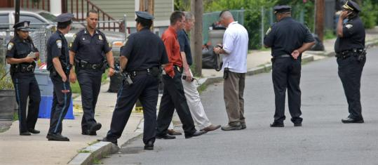 Police gathered at the scene of the attack, in which a woman was bitten trying to protect her dog.