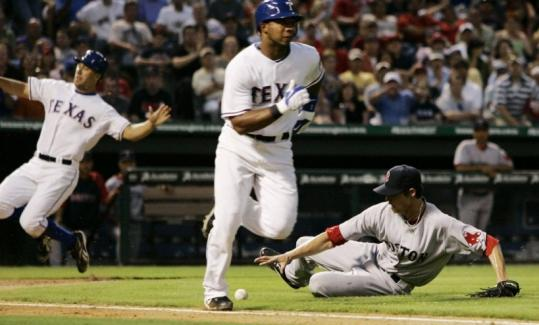 David Murphy (left) scores on a suicide squeeze bunt by Elvis Andrus, who scampers safely to first as Sox pitcher Clay Buchholz fields the ball.