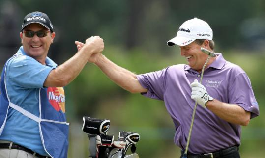Fred Funk and his caddie celebrate his eagle on the 18th hole that gave him a 3-shot lead in the Senior British Open and a tournament-record 11 under through 36 holes.