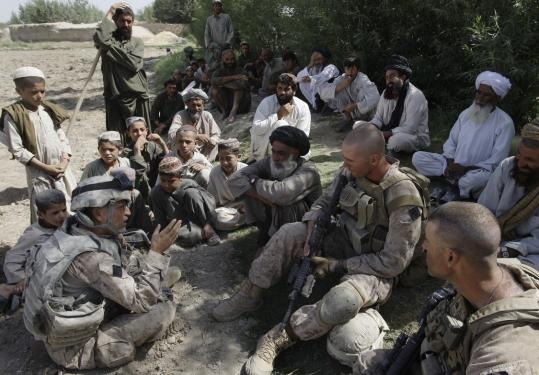 Josh Habib (far left), a 53-year-old translator, along with two Marines, spoke to Afghan villagers. He has hiked in extreme heat, and said this is not the job he signed up for.