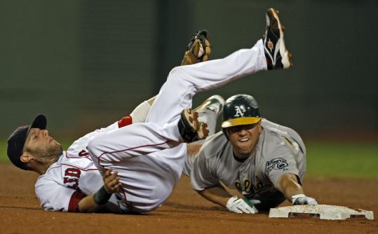 Dustin Pedroia takes a tumble but tags out Jack Cust, who was trying to stretch a single.