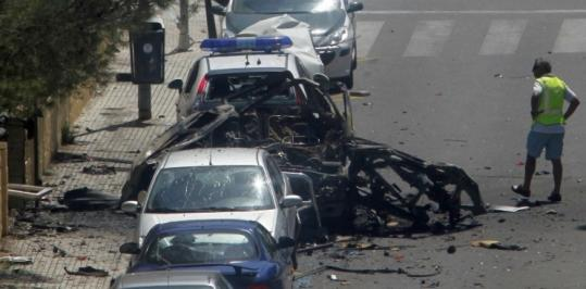An investigator checked out the wreckage of a car in Palmanova, Spain, yesterday. Two officers were killed.