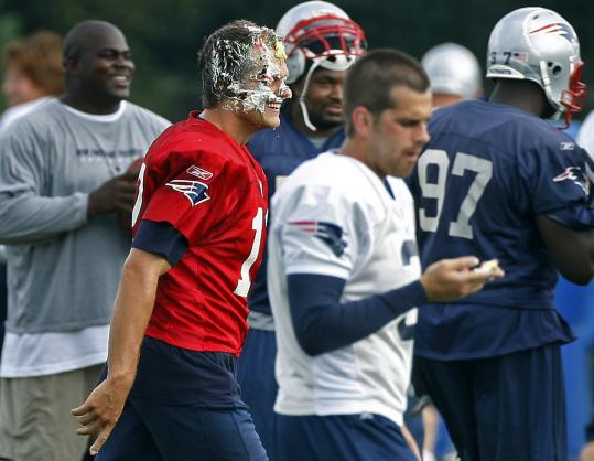 Tom Brady, with a face full of cake, takes his birthday hijinks in good fun yesterday at practice in Foxborough.