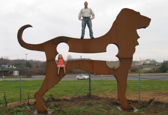 Artist Dale Rogers and daughter Beatrice, 6, perch on his distinctive metal statue along Interstate 495 in Haverhill.