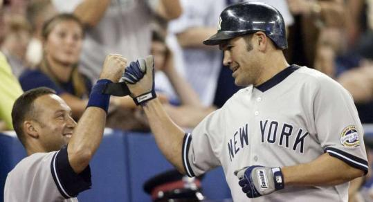 Johnny Damon celebrates his ninth-inning home run with Derek Jeter.