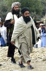 A photo from 2004 shows Pakistani Taliban chief Baitullah Mehsud (right) escorted by a guard as he arrived for a meeting in the South Waziristan tribal region.