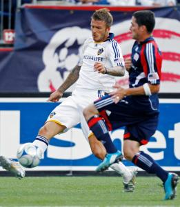 Galaxy's David Beckham (left) controls the ball in front of Revolution's Jay Heaps.