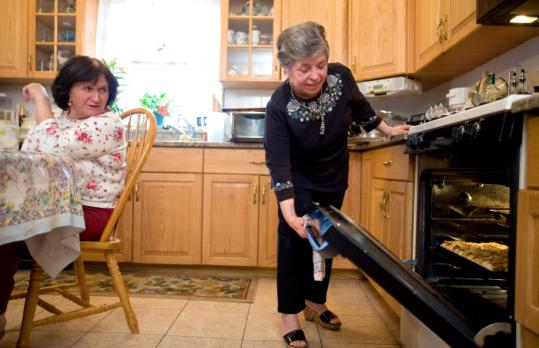 Twice a month, Concetta Cucinotta (seated) and Angela Molinario spend the day making pizza for their family in the kitchen of Cucinotta's home in Dedham.