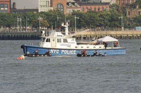 Divers in inflatable boats maneuvered yesterday near where the wreckage of a small plane was found, off Hoboken, N.J.