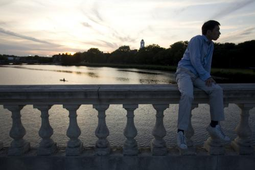 Haidong Yuan, a post-doctorate student at MIT, watched the tango dancers on the bridge as the sun set.