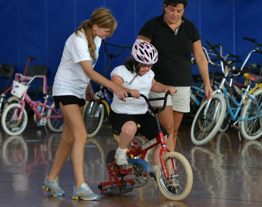 Volunteer Rachel Flynn helps Kelly McCowan of Scituate on the bike, while Kelly's mother, Sue, stands ready to lend a hand.