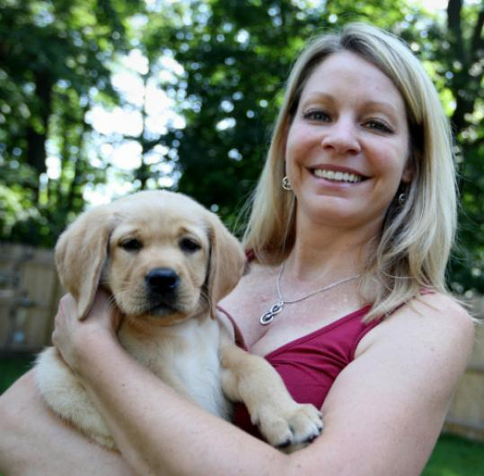 Dog walker Nancy Pickwick at her home in Scituate with Peaches the puppy.