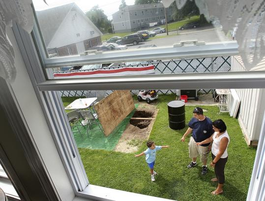 Dave and Brenda Mattos and their son Ethan, 3, stood near a sinkhole in their New Bedford backyard.