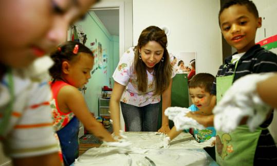 Jacqueline Bedoya and her young charges use shaving cream to clean up after a painting exercise at Bedoya's day-care center in Chelsea.