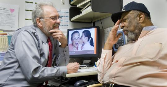 Group Health clinic's Dr. Harry Shriver with patient Grover Williams in Bellevue, Wash. The co-op has helped the state maintain low insurance rates.