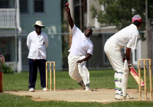 Everton Holder bowled the ball to batter Vasu Ram while umpire Cecil Butcher watched during a cricket match between Star Cricket Club and Trinidad and Tobago International on Aug. 15.