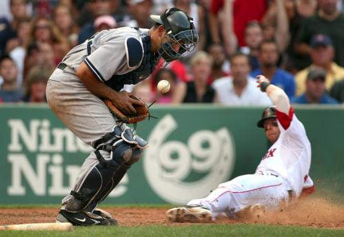 Dustin Pedroia slides home safely in front of Yankees catcher Jorge Posada in the sixth inning.