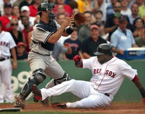 David Ortiz slides in safely beneath Yankees catcher Jorge Posada on a Jason Bay RBI single in the first inning.