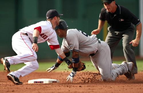 Red Sox second baseman Dustin Pedroia shuffles to tag out Robinson Cano, who tried to stretch a wall ball to left into a double, but was gunned down by Jason Bay's throw.