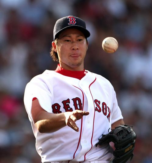 Red Sox starting pitcher Junichi Tazawa throws the ball to first base to retire Melky Cabrera in the fourth inning.