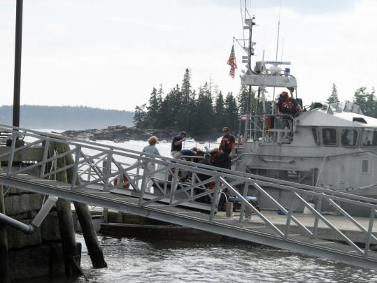 A Coast Guard boat arrived Sunday to try to rescue people who were knocked into the ocean by a large wave near Acadia National Park. They rescued two, but Clio Axlerod, 7, died.