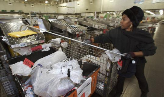 Thanks to the recession and rising production and shipping costs, retailers are shrinking catalogs and slashing mailing lists, leaving less sorting for postal employees such as Lucretia Thomas, seen working at a distribution center in Los Angeles.