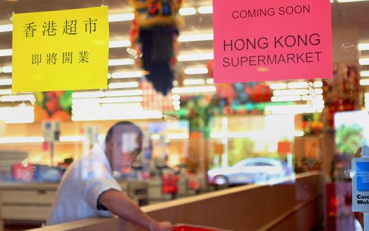 Sign announcing the arrival of New York's Hong Kong Supermarkets appears in the window of the Super 88 in Dorchester.