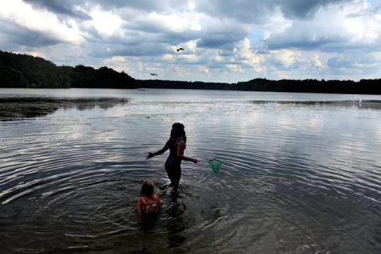 Two young girls tried to net some fish Monday in Lake Cochituate in Natick, which some say could be adversely impacted by stimulus money plans.