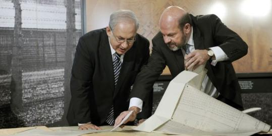 Prime Minister Benjamin Netanyahu of Israel (left) and German historian Ralf Georg Reuth studied Auschwitz blueprints yesterday in Berlin.