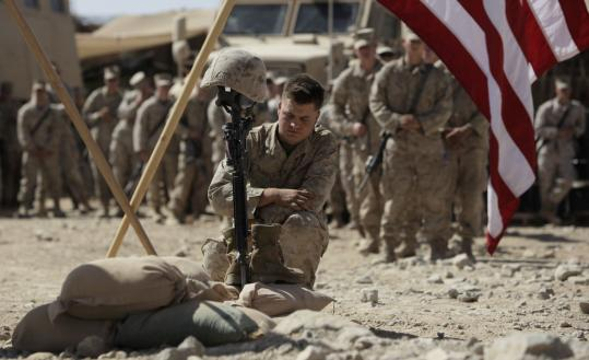 Marine Corporal Russell paid his respects yesterday to Lance Corporal Joshua Bernard at a memorial service in Helmand Province in Afghanistan. Bernard was mortally wounded during a Taliban ambush Aug. 14.