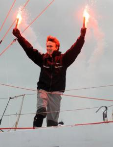 Mike Perham, 17, celebrated with flares yesterday at the finish line off the coast of Cornwall, England.