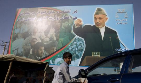 The Afghan election commission says Hamid Karzai (in poster) is nearing the 50 percent mark that would let him avoid a run-off.