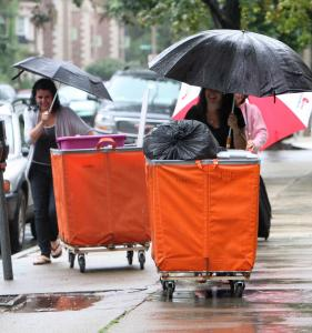 BU freshman Rose Goldfarb (left) and her family dodged puddles on Bay State Road yesterday as they moved Rose's belongings into her dorm room. Rainfall was as high as 5 inches in Eastern Massachusetts yesterday.