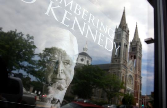The reflection of the Basilica of Our Lady of Perpetual Help was seen in a storefront window in Mission Hill, which displayed a poster of the late Senator Edward M. Kennedy, whose funeral was held at the church Saturday.