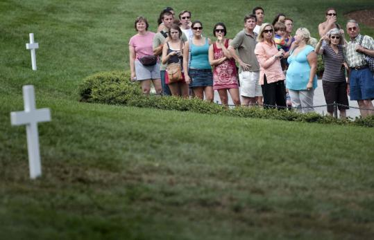 Hundreds mourned at the grave of Senator Edward M. Kennedy. The grave of his brother, Robert, is in background.