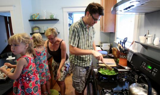 Karen Pfefferle and Geoff Cisler prepare food with their 4-year-old twins, Lena (left) and Anna.