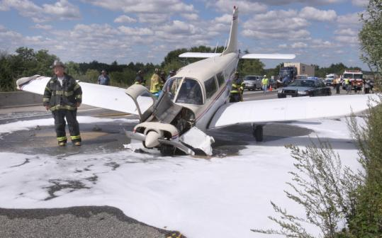 A firefighter stood near the Piper Cherokee that landed southbound on Interstate 495 yesterday in Mansfield.