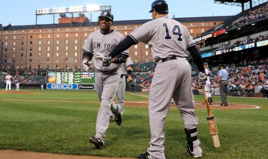 Yankees&#8217; Robinson Cano is congratulated by Eric Hinske after his second inning home run against the Orioles at Camden Yards.