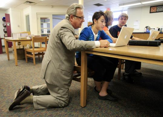 John Couch, Apple Inc.'s vice president for education, worked yesterday with Brien Crisci, a sophomore at Hall-Dale High School, as she tried out her new laptop in Gardiner, Maine.
