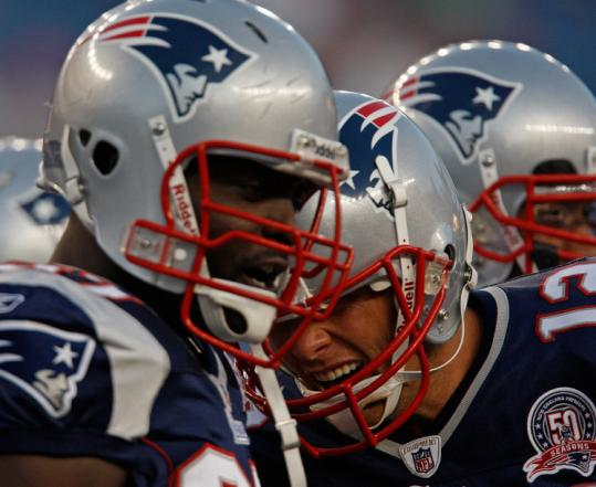 Tom Brady (right) didn't play, but that didn't stop he and a teammate from putting their heads together before kickoff.