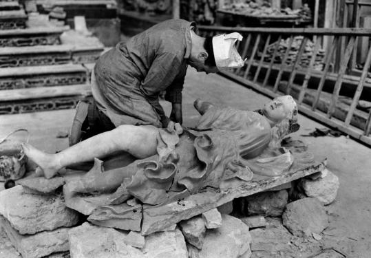 A laborer repairs a statue at the church of Casa Professa in Palermo, damaged in an Allied bombing raid in 1943.