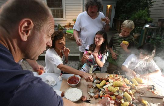 "WFNX's Henry Santoro (back, center) with friends and family enjoying his signature dish, ""the Dump,'' a boil of potatoes, corn, sausage and seafood. No plates or silverware are needed."