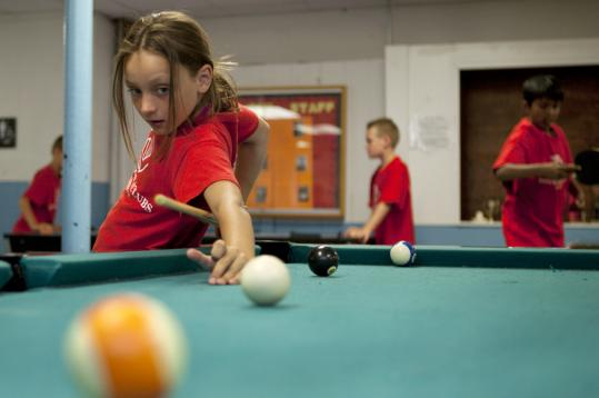 Brooke Bohn, 9, of Hudson, tries a fancy shot at her local Boys & Girls Club of MetroWest, which is seeing enrollment rise even as its funding falls.