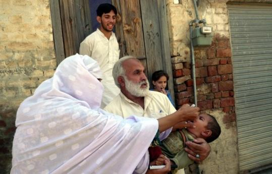 A Pakistani volunteer administered polio vaccine drops to a girl in Mingora in the troubled Swat Valley yesterday.