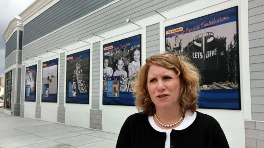 Leslie Cohen, vice president of development for Samuels & Associates, talks about the wall (in background) and wayside panels installed around the Hingham Shipyard that tell the story of the shipyard's involvement in WWII.