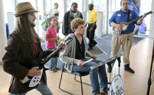 """Dan Zunk (left), Spencer Fink, and Oliver Narragansett tried out The Beatles: Rock Band game yesterday at Best Buy in Boston. """"Man, I could play this all day,'' said Zunk, a Berklee College of Music student. The game is available for Microsoft Xbox 360, PlayStation 3, and Nintendo Wii."""