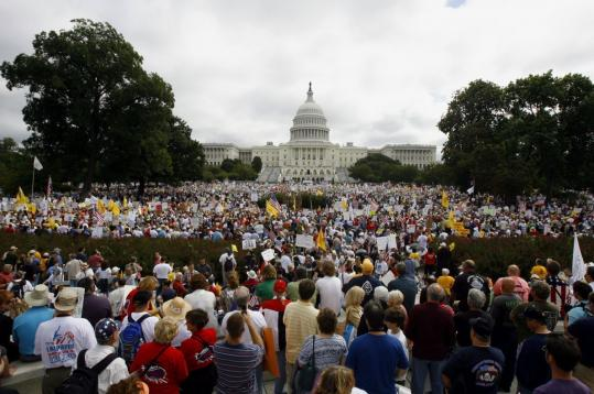 """Bearing signs that said """"Enough! Enough!'' or """"Go Green Recycle Congress,'' tens of thousands marched in Washington against the president's health care plan and federal spending."""