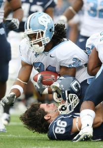 UConn's Alex Molina loses his helmet but still manages to bring down UNC's Johnny White.