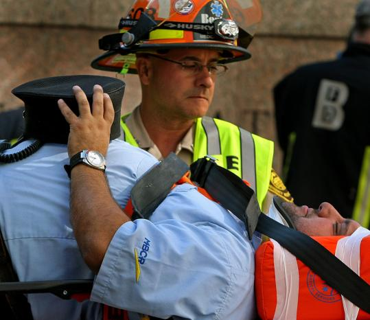 Rescuers moved an injured man to an ambulance yesterday following a commuter rail accident at South Station. Eighteen passengers suffered mostly minor injuries in the low-speed crash.